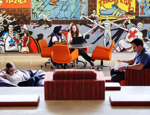 Students sitting in lounge area with graphic mural backdrop